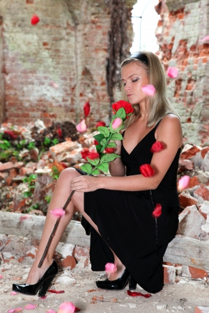 lovely woman with rose under falling petals at old house Stock Photo - 15980527