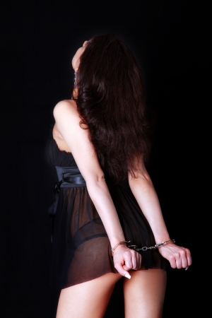 handcuffed: woman back with handcuff Stock Photo