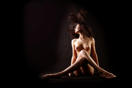 nude girl with flapping hairs against black background