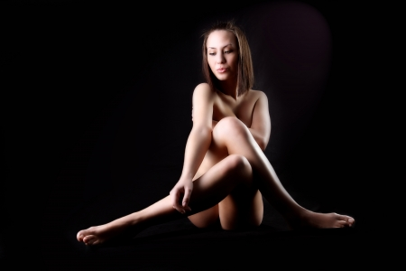 girl sitting against black background Stock Photo - 15948035