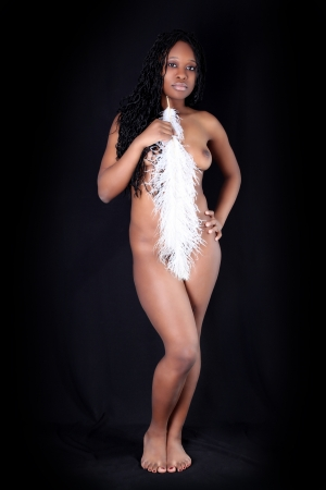 afro american nude: young afro-american woman with white feather against black background