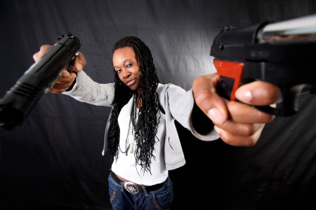 young afro-american woman with gun against black background photo
