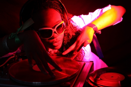 cool afro american DJ in action under yellow-red light photo