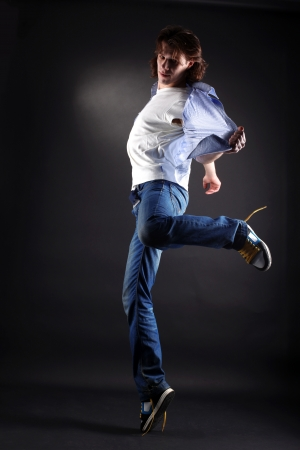 young man modern dancer in action against black photo