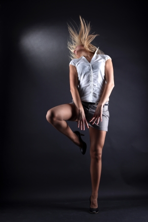 blondie: young woman modern dancer in action against black