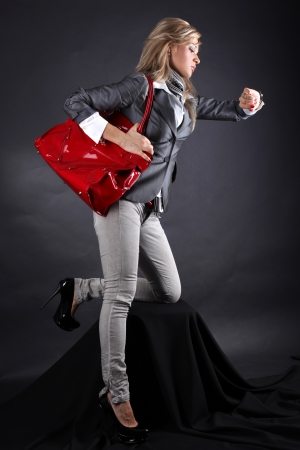 fashion young woman with red bag looking at watch photo