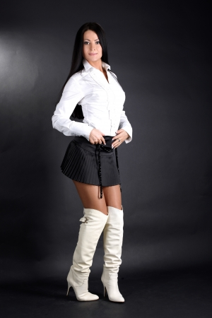 fashion young woman in white shirt and boots and black skirt photo
