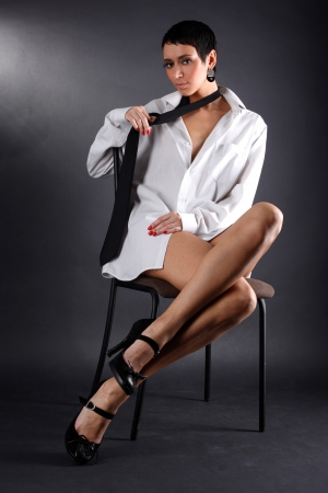 lovely young fashion model in big man shirt and tie sitting in chair against black photo