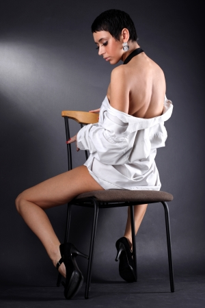 lovely young fashion model in big man shirt sitting in chair against black photo
