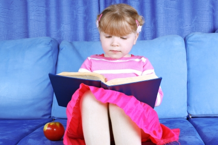 girl reading book with apple at sofa  photo