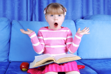 surprised little girl with apple and books in sofa photo