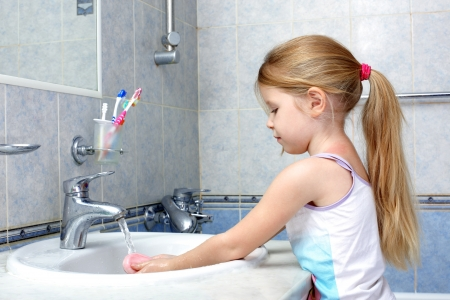 Little girl washing in bathroom Stock Photo