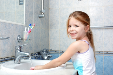 Little girl washing with soap in bathroom photo