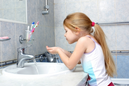 bathroom mirror: Little girl washing in bathroom Stock Photo