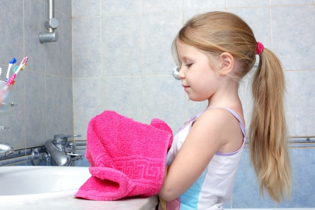 Little girl taken towel after washing in bathroom photo
