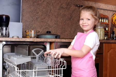 little girl taken clear glass from dishwasher in the kitchen  photo