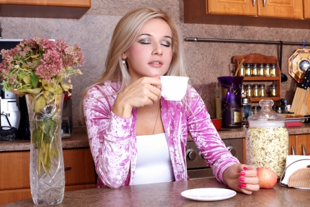 Woman sniffing the scent cup of hot drink, breakfast in the kitchen