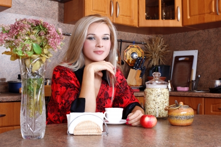 Woman with jasmin petals, apple and cup of hot drink in the kitchen photo