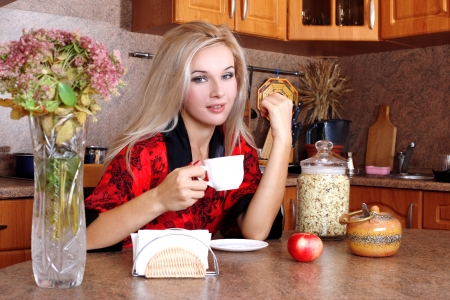 woman breakfast with apple and cup of hot drink in the kitchen photo