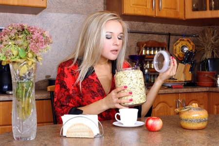 Woman taken jasmin petals for breakfast with apple and cup of hot drink in the kitchen photo
