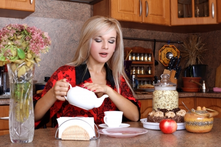 woman breakfast with apple, teapot and cup of hot drink in the kitchen photo