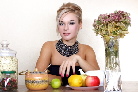 woman with cup, jasmin petals, lemon, apple, tea and autumn flowers against yellow wall at home photo