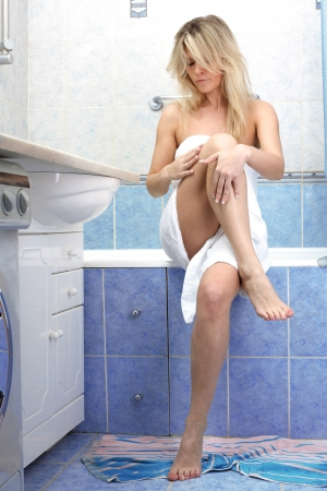Young woman applying cosmetic cream on leg in bathroom photo