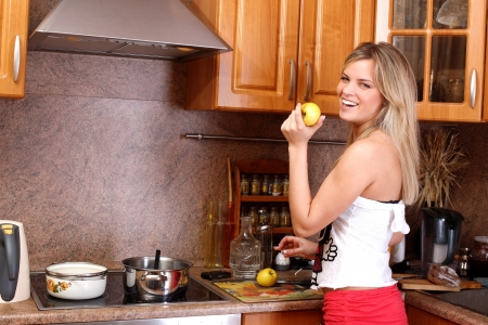 boiling point: funny woman cooking dinner and holding apple in the kitchen
