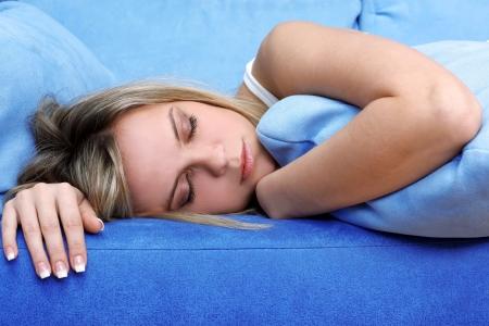 Young woman sleeping on blue sofa photo