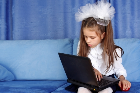 hard day in learning - girl with laptop and red apple in sofa photo