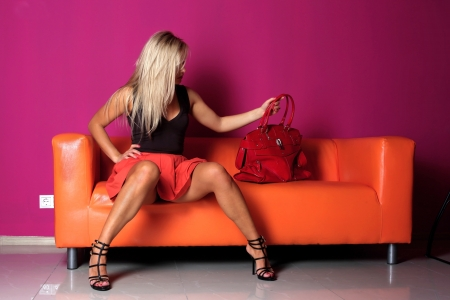 woman seated on a sofa with red bag photo