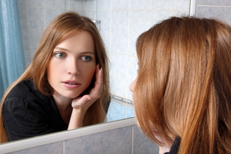 young woman in bath at front of a mirror inspected skin Stock Photo - 16049486