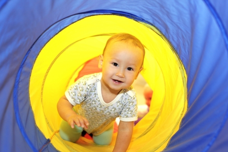 Baby playing in tube photo