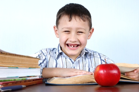 smiling schoolboy without several tooths with red apple and books Stock Photo - 15987942