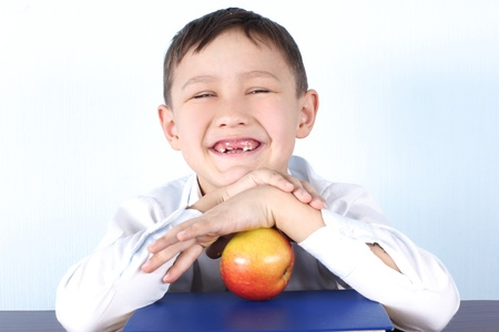 smiling schoolboy without several tooths with red apple and book Stock Photo - 15982520