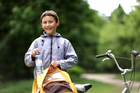 Young boy with bicycle with clear water relaxing outdoors photo