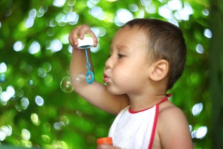 Boy blowing soap bubbles photo