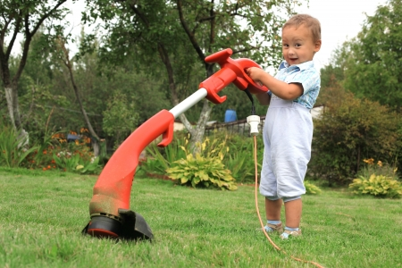 young baby boy with trimmer in garden photo