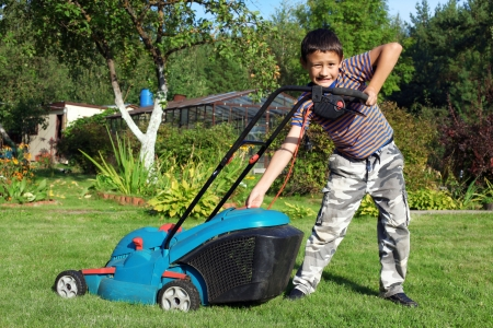 Little Boy Gardener mowing the lawn photo