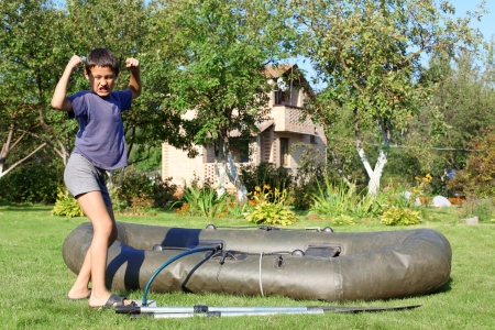 boy inflate boat and show power photo