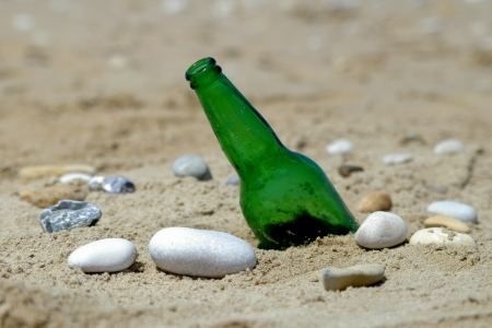 bottle on sand near water photo