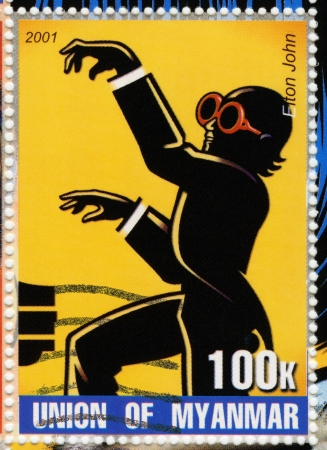 MYANMAR - CIRCA 2001   stamp printed in Myanmar show funny cartoon pic with Elton John , circa 2001 Stock Photo - 16042842