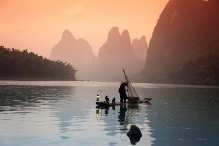 Chinese man fishing with cormorants birds, Yangshuo, Guangxi region, traditional fishing use trained cormorants to fish photo