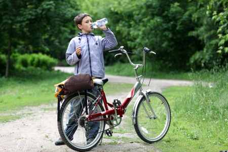 Young boy with bicycle with drinking clear water photo