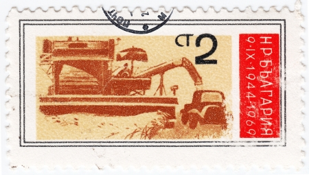 BULGARIA - CIRCA 1969 : stamp printed in Bulgaria shows a grain harvester combine in harvest time, circa 1969 Stock Photo - 16393291