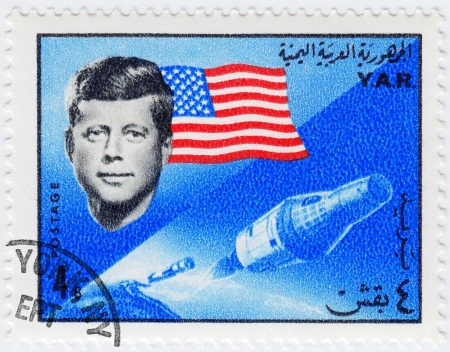 YAR - CIRCA 1970 : Stamp printed in YAR shows John F Kennedy background usa flag and spaceshuttle , circa 1970