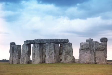 megalith: Stonehenge historic site on green grass under blue sky    Stock Photo