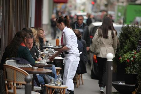 PARIS - 27. APRIL Parisern und Touristen genießen Essen und Getränke im Café Bürgersteig in Paris, Frankreich am 27. April 2013 ist Paris eine der am dichtesten besiedelten Ballungsräume in Europa Standard-Bild - 19995072