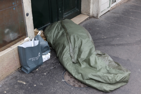 loitering: PARIS - MAY 1   Homeless man curled up under a plastic tarpaulin, asleep on the street, May 1, 2013 in Paris, France  Today, France has 130,000 homeless, and every day one of them dies Editorial