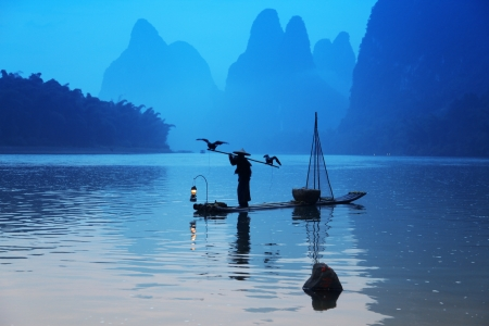 cormorants: Chinese man fishing with cormorants birds in Yangshuo, Guangxi region Stock Photo